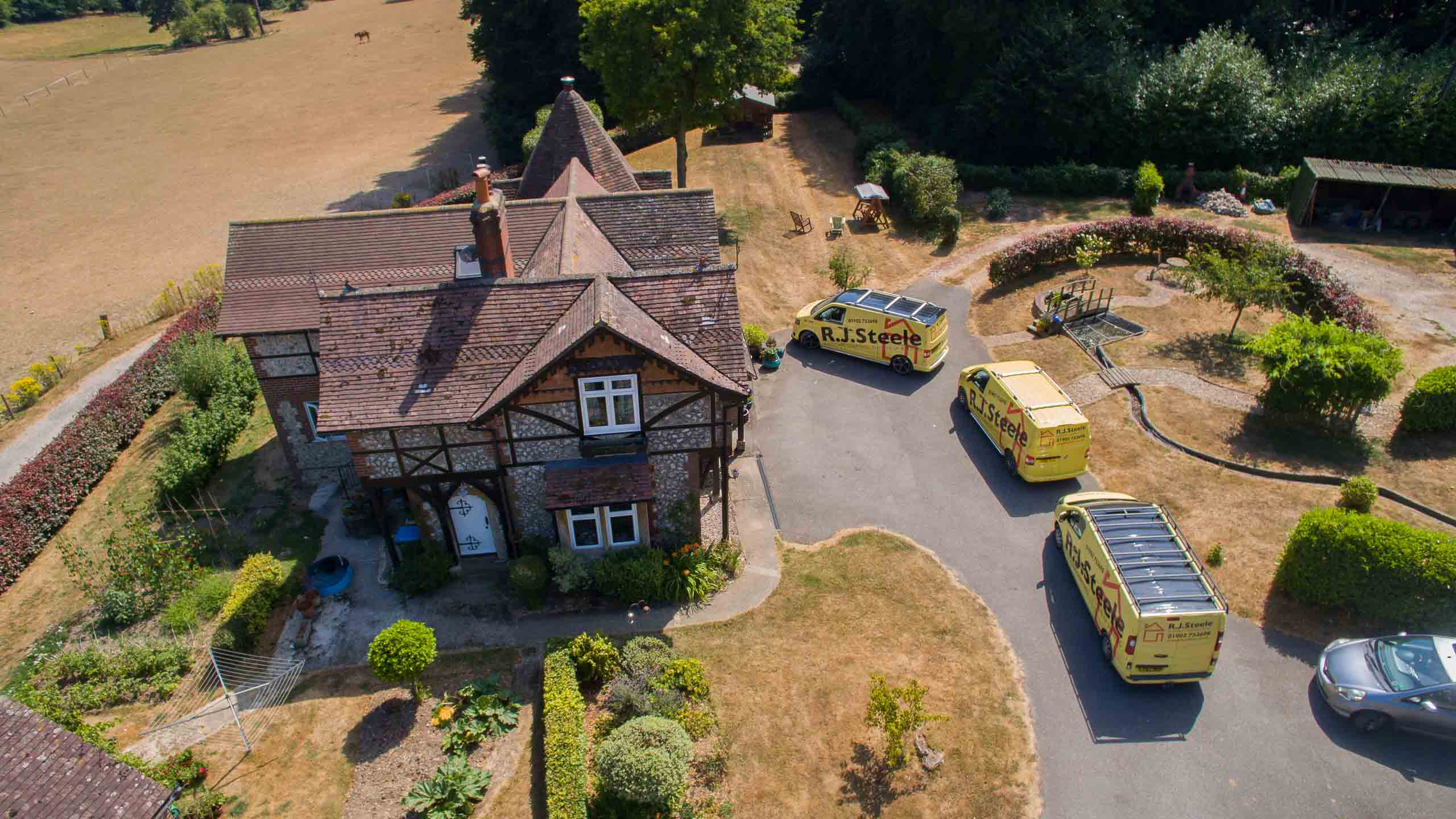 aerial view of three work vans arriving at job - building work by RJ Steele builders in Sussex