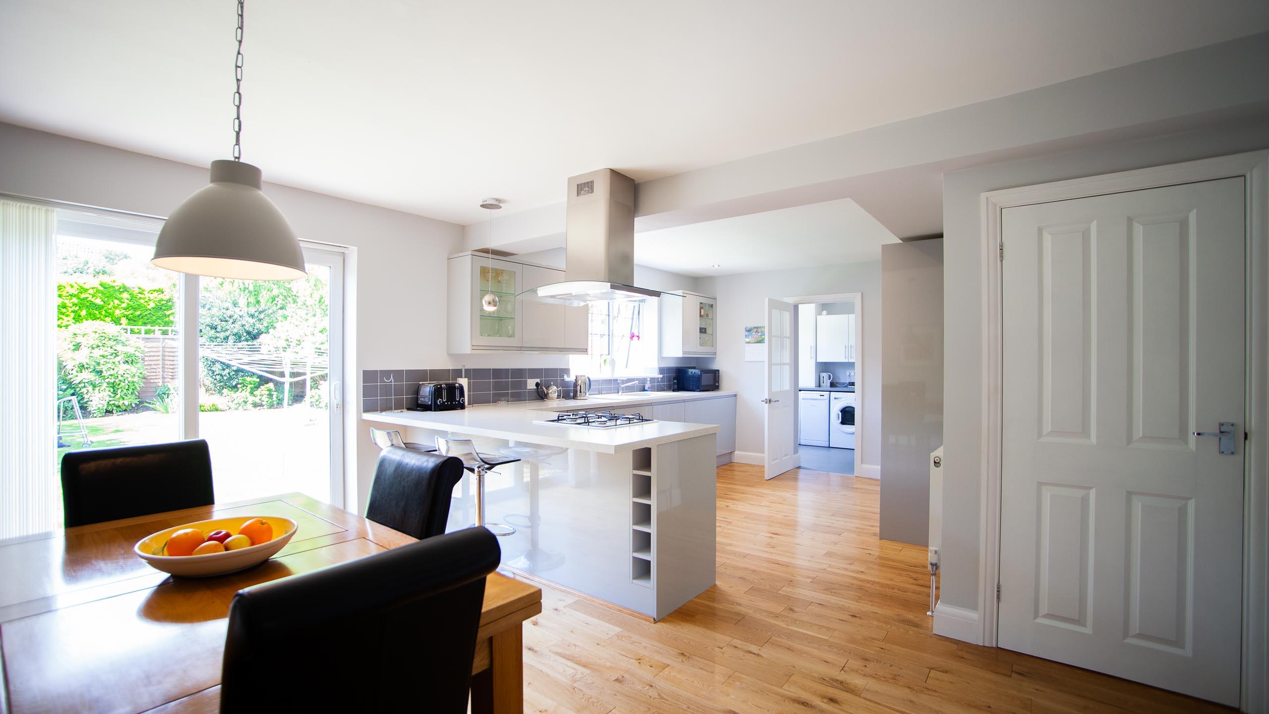 modern kitchen/diner with sliding doors to garden - kitchen installation by RJ Steele builders in Sussex